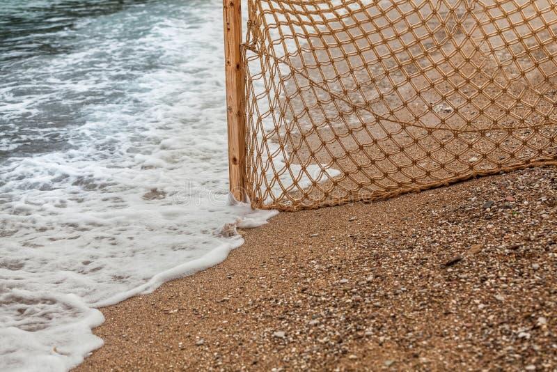 Filet de pêche sur la plage sablonneuse aux vagues de mer images libres de droits