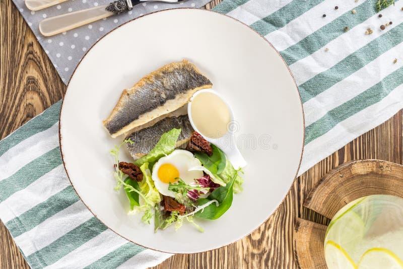 Filet de poisson blanc frit à l'oeuf frit et légumes sur assiette blanche sur table en bois photo libre de droits