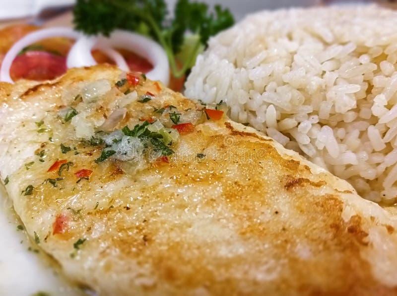 Filet de poissons grillé avec de la sauce à sauce au jus servie avec du riz image libre de droits