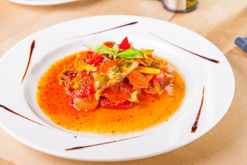 Filet de poissons haut étroit de ragoût avec des légumes décorés de la feuille de basilic du plat blanc sur la table woodan servi photos libres de droits
