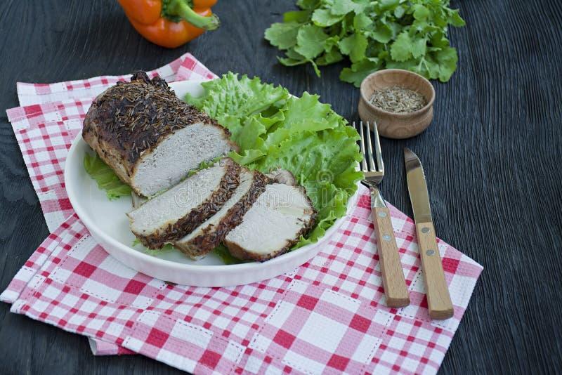 Filet de porc cuit au four en épices coupées en tranches d'un plat blanc avec de la salade verte Fond en bois fonc? photo stock