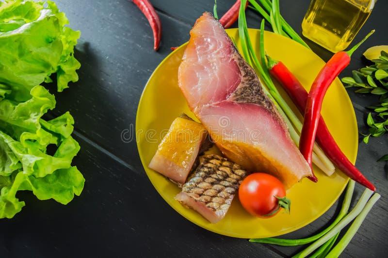 Filet de porc de carpe argentée fumée à la bière d'un plat jaune avec des verts Vue supérieure Bois noir de fond Plan rapproché photos stock