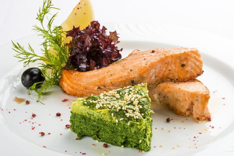 Filet frit des saumons avec des épinards D'un plat blanc photographie stock