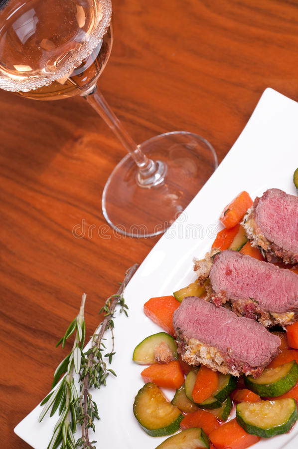 Filet of lamb with herbs and a glass of wine stock image
