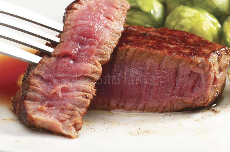 Filet mignon. Juicy filet mignon cutted on plate with brussel sprout royalty free stock images