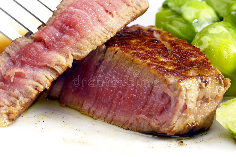 Filet mignon. Juicy filet mignon cutted on plate with brussel sprout stock image