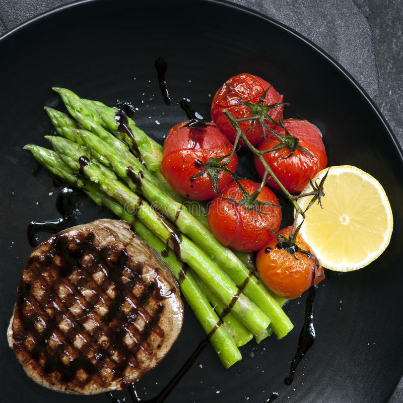 Filet Mignon with Asparagus and Cherry Tomatoes. Filet mignon grilled beef steak, with asparagus and cherry tomatoes. On black plate royalty free stock image