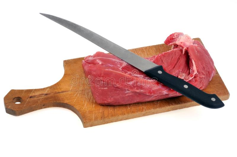 Filet mignon of pork on a cutting board on a white background. Closeup on raw meat with a knife on a wooden kitchen utensil on a white background royalty free stock image
