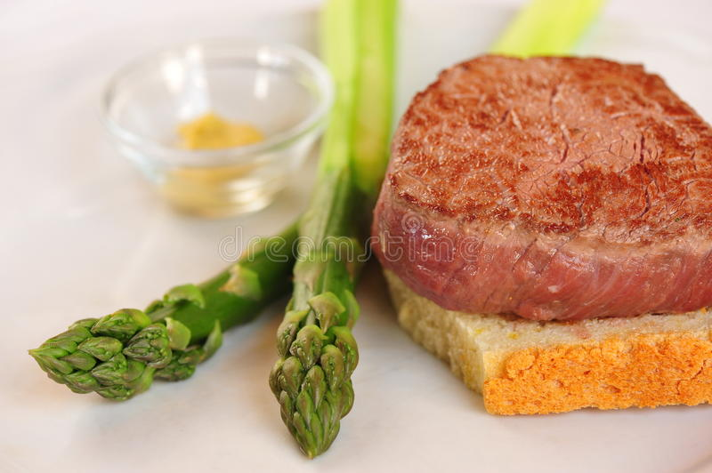 Filet Mignon. Steak on bread with Asparagus stock photo