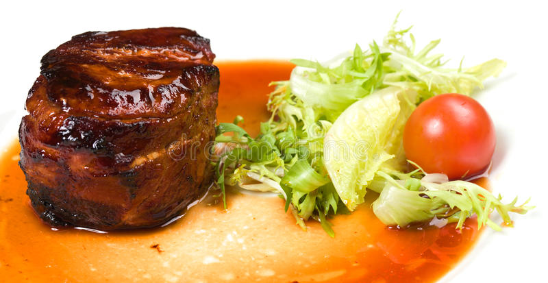 Filet mignon with vegetables. On a white plate royalty free stock image