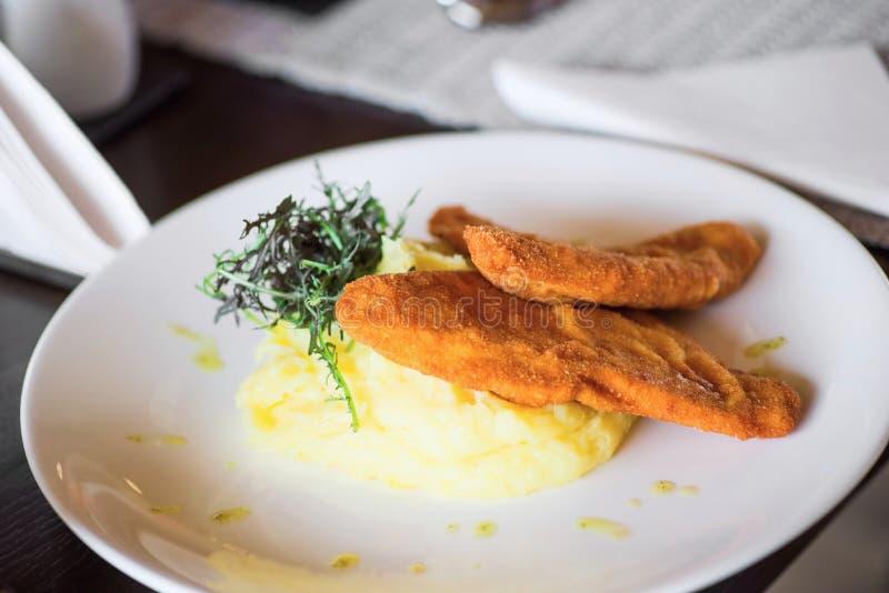Filet pané de poulet avec de la purée de pommes de terre et la feuille de rucola images libres de droits