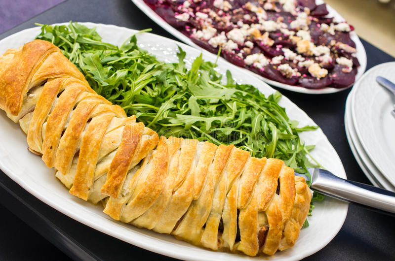 Filet in puff pastry. Served with beet roots carpaccio and arugula salad stock images