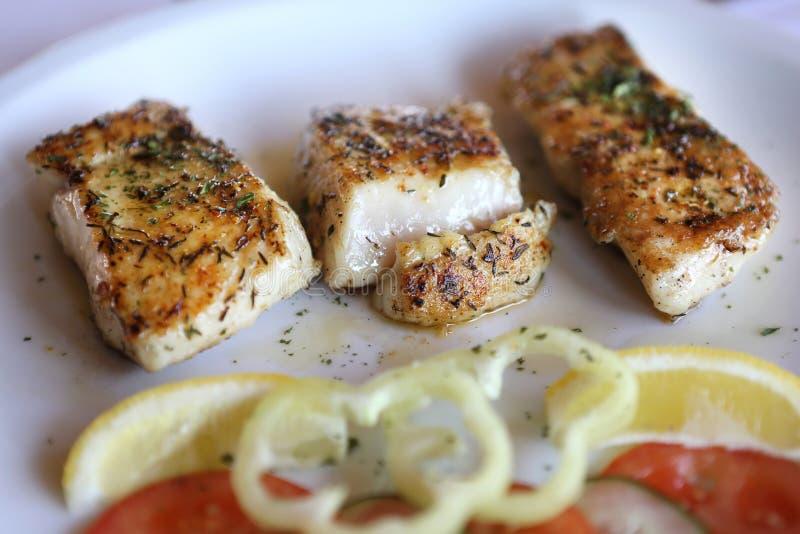 Filet rôti de poisson-chat servi avec des légumes images stock