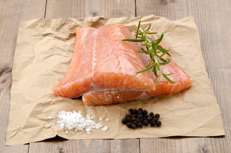 Filet saumoné frais avec le romarin sur le papier brun photo stock