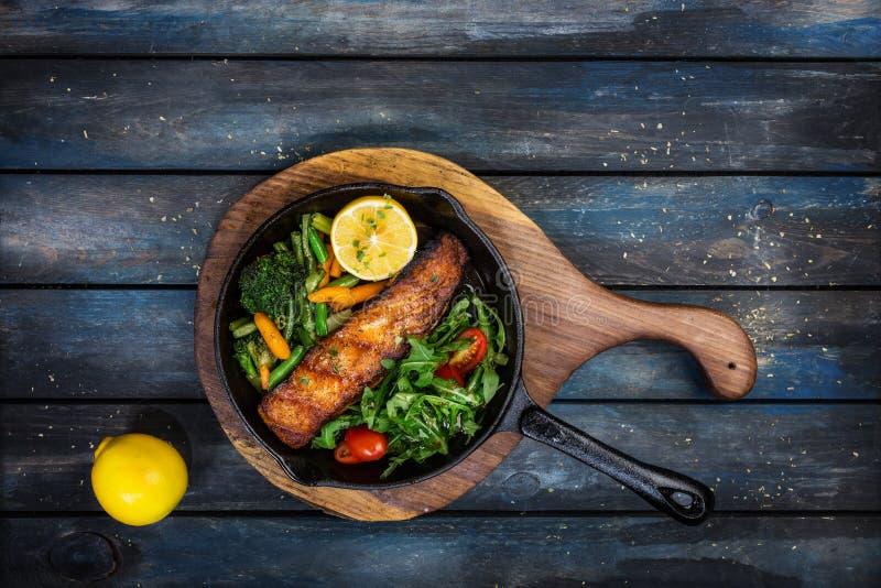 Filet saumoné grillé dans une poêle, légumes, arugula avec un citron photo stock