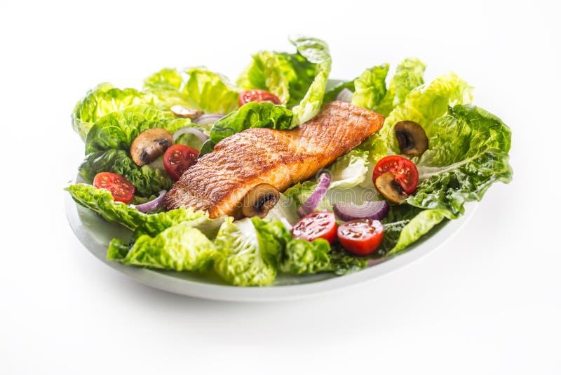 Filet saumoné rôti avec de la salade de légume frais d'isolement sur le fond blanc photographie stock libre de droits