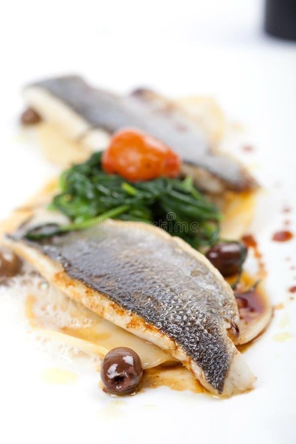 Filet van overzeese baarzen met ravioli, spinazie en olijven stock foto