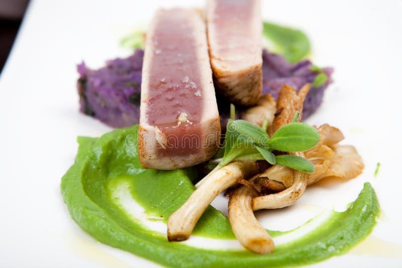 Filet van tonijn met oesterpaddestoelen, aardappels en erwtenpuree royalty-vrije stock foto