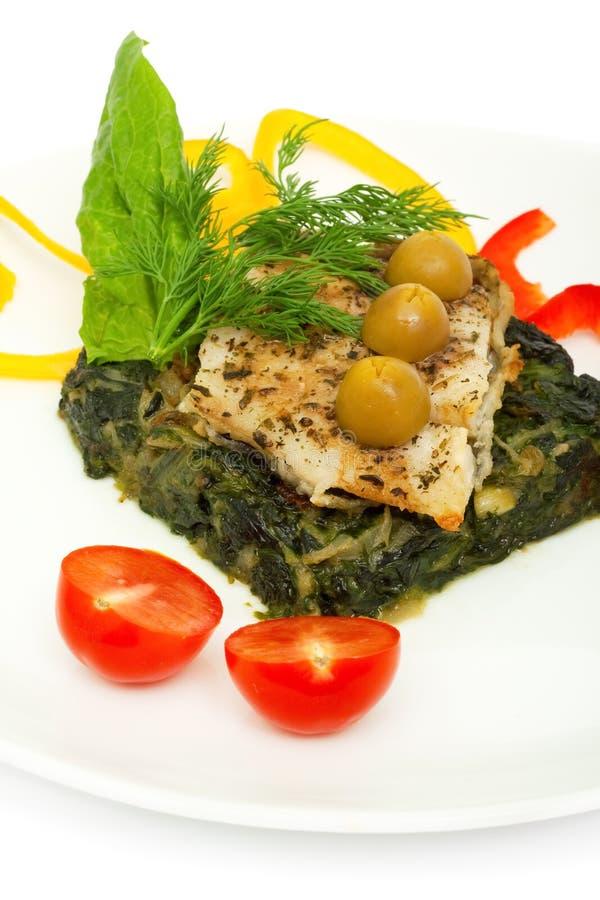 Filet van vissen roosterde en sauteed spinazie stock afbeelding