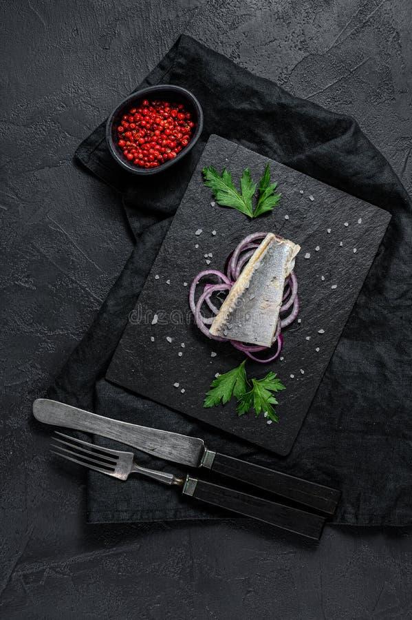Filet ze śledzia solonego z pietruszką i cebulą czerwoną Na czarnym tle rutynowym Widok z góry Spacja dla tekstu obraz royalty free