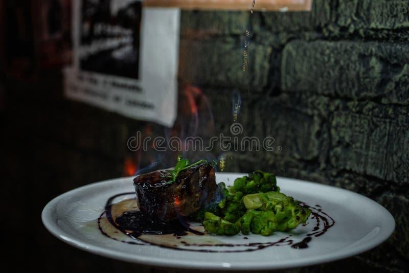 Filete apetitoso en llama azul con bróculi cocido en salsa de vino La porción original de filete en el restaurante fotografía de archivo