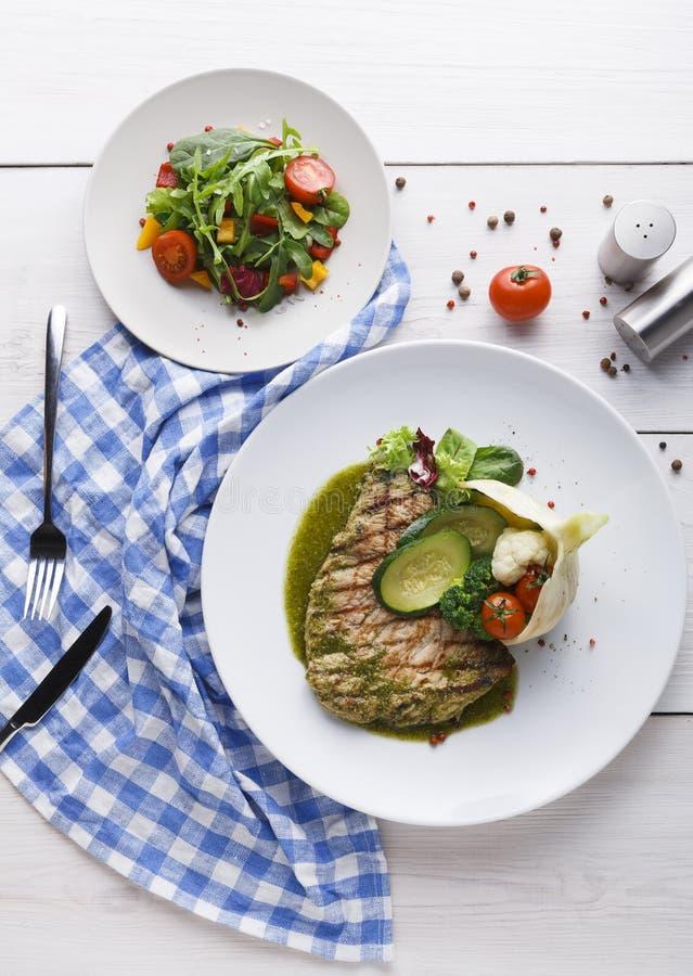 Filete asado a la parrilla apetitoso y ensalada vegetal sana fotos de archivo