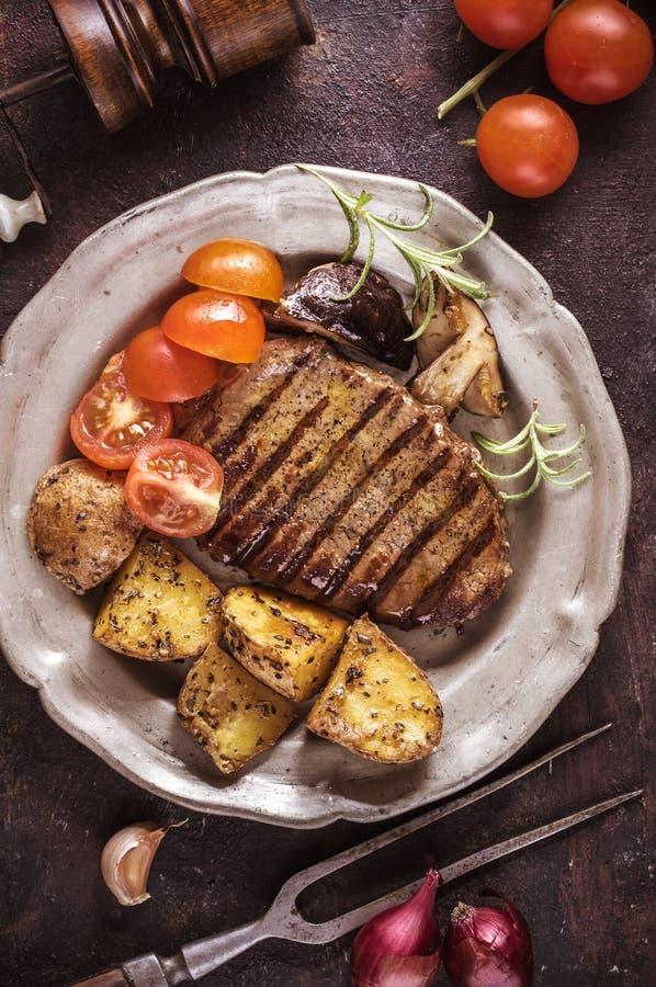 Filete asado a la parrilla con la patata cortada y los tomates verticales fotos de archivo