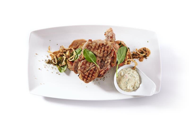 Filete asado a la parrilla del cerdo con la patata y la salsa de tártaro asadas fotografía de archivo