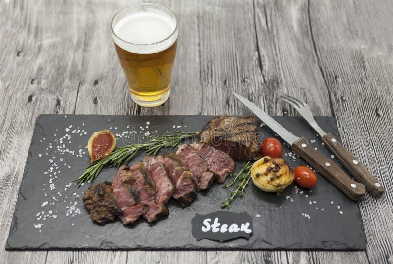 Filete asado a la parrilla del striploin en una placa de piedra con un vidrio de cerveza con una bifurcación y un cuchillo fotos de archivo