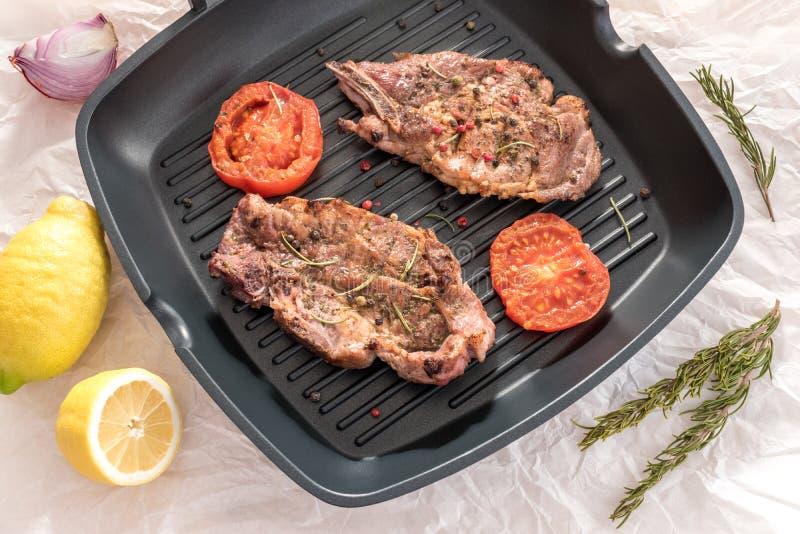 Filete asado a la parrilla en la cacerola de la parrilla con los tomates y el limón en la parte posterior del blanco fotografía de archivo libre de regalías
