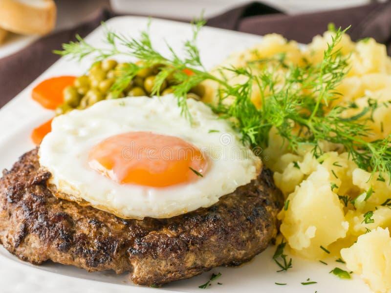 Filete con el huevo frito y el primer de los purés de patata foto de archivo