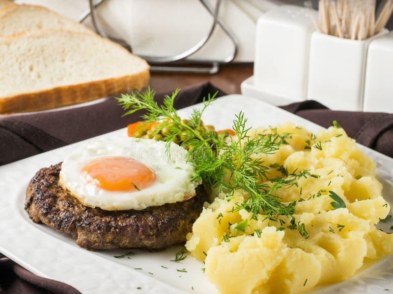 Filete con el huevo frito y el primer de los purés de patata imagen de archivo