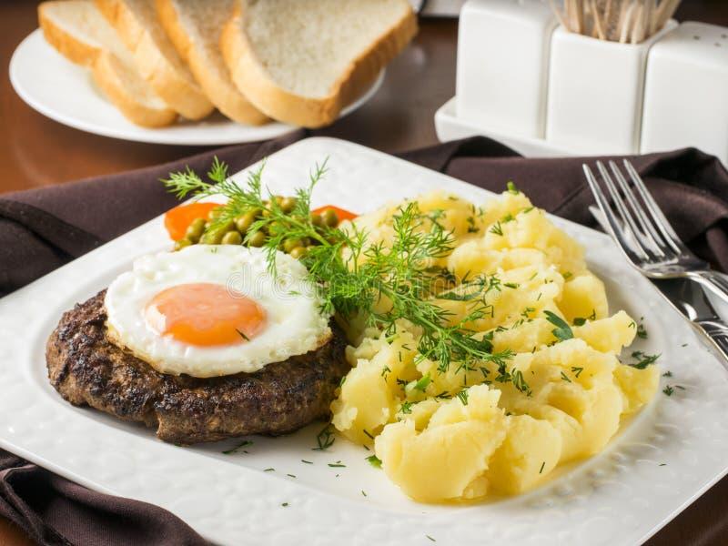 Filete con el huevo frito y el primer de los pur?s de patata foto de archivo libre de regalías