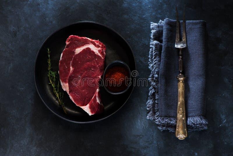 Filete crudo Ribeye en placa, la bifurcación de la carne, hierbas y especias fotos de archivo