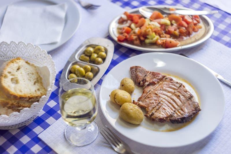 Filete de atún acompañado con las patatas, aceitunas, ensalada del tomate, brea foto de archivo