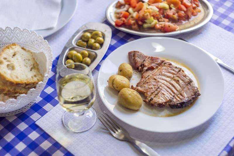 Filete de atún acompañado con las patatas, aceitunas, ensalada del tomate, brea imágenes de archivo libres de regalías