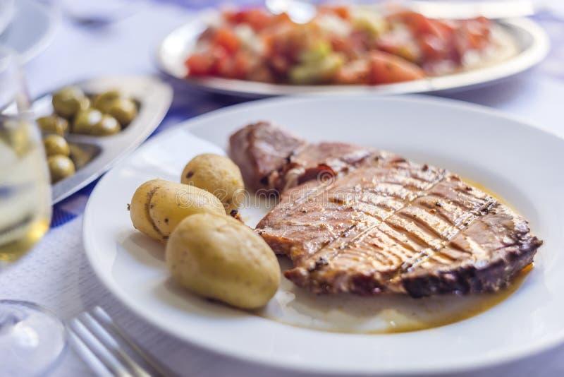 Filete de atún acompañado con las patatas, las aceitunas, la ensalada del tomate y w fotos de archivo libres de regalías