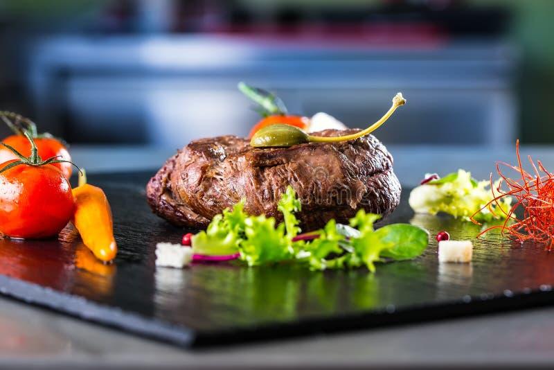 Filete de carne de vaca asado a la parrilla con la decoración vegetal Filete de porterhouse asado a la parrilla en tablero de la  imagen de archivo libre de regalías