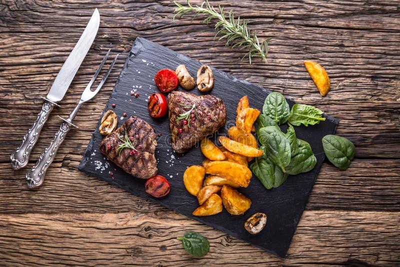 Filete de carne de vaca asado a la parrilla con romero, sal y pimienta en vieja tabla de cortar beef fotos de archivo libres de regalías
