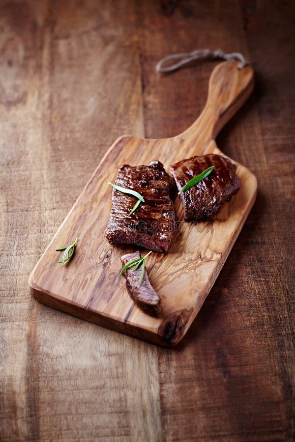 Filete de carne de vaca asado a la parrilla en una tajadera fotos de archivo