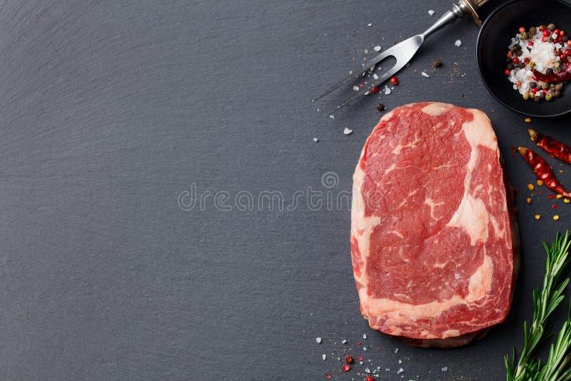 Filete de carne de vaca crudo con las especias y los ingredientes para cocinar Visión superior Copie el espacio imagen de archivo