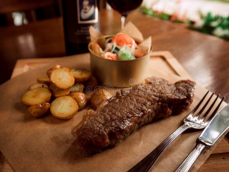 Filete de carne de vaca jugoso con las patatas y el vino imágenes de archivo libres de regalías