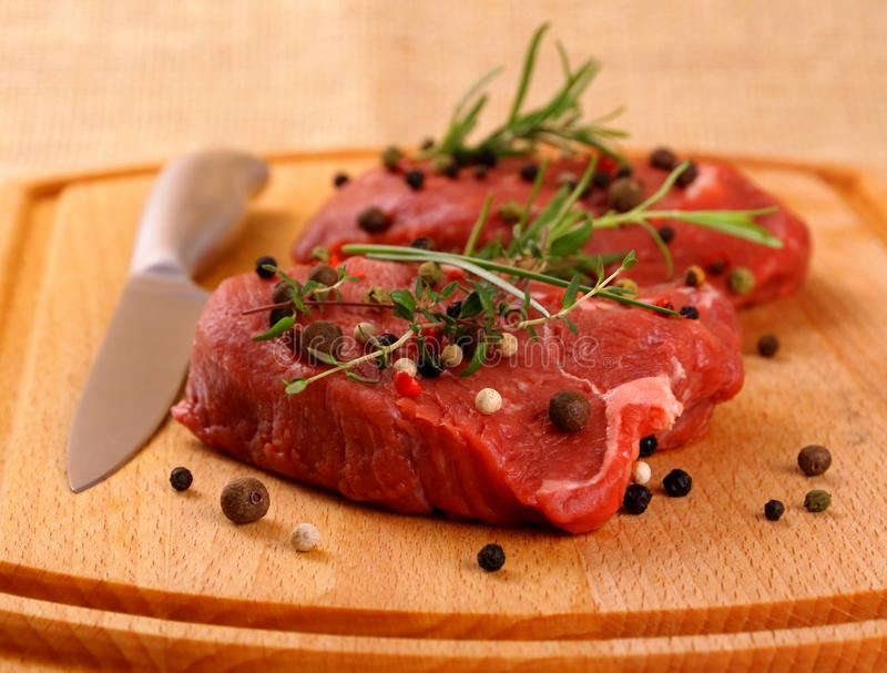 Filete de carne de vaca jugoso dos con las especias y el cuchillo de acero fotografía de archivo