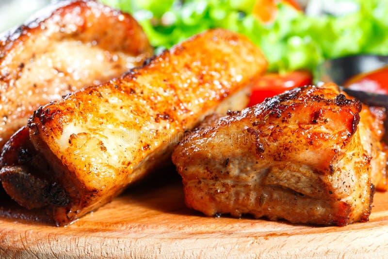 Filete de carne de vaca asado a la parrilla con la ensalada, los tomates y la salsa de las verduras frescas en tabla de cortar de foto de archivo libre de regalías