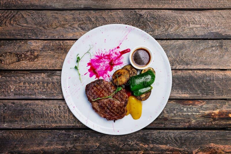 Filete de carne de vaca asado a la parrilla en una placa blanca con las verduras asadas a la parrilla imágenes de archivo libres de regalías