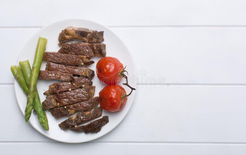 Filete de carne de vaca asado a la parrilla en una placa blanca y un fondo, una endecha del plano y un espacio blancos de la copi fotografía de archivo