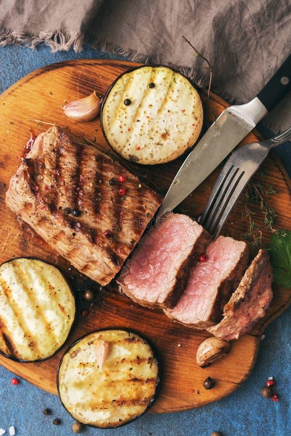 Filete de carne de vaca asado a la parrilla en una tabla de cortar con las verduras, fondo azul Visión superior, endecha plana imagenes de archivo