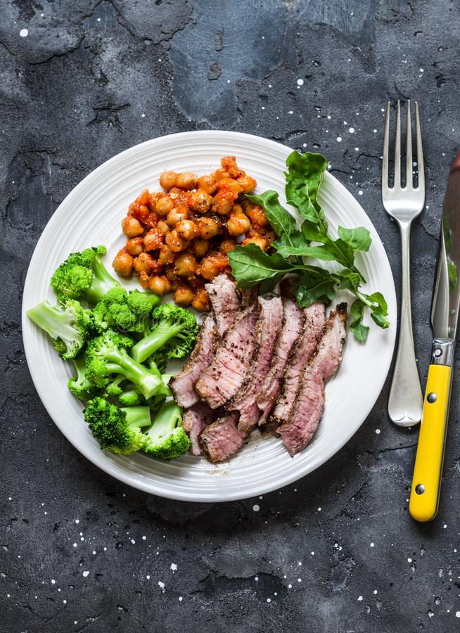 Filete de carne de vaca asado a la parrilla, garbanzos guisados picantes, bróculi - almuerzo sano delicioso en un fondo oscuro, v foto de archivo libre de regalías