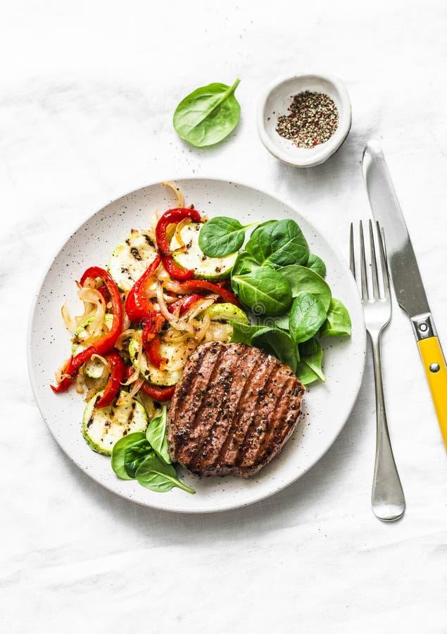 Filete de carne de vaca con las verduras asadas a la parrilla, la pimienta dulce, el calabacín y la espinaca fresca en un fondo l fotografía de archivo
