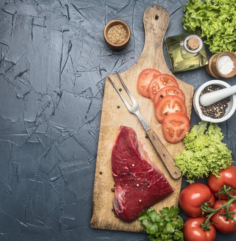 Filete de carne de vaca crudo apetitoso con los tomates y bifurcación para la carne en una tabla de cortar del vintage, rodeada p imagenes de archivo